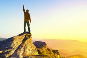 Un Gagnant au sommet d'une montagne regarde le soleil levant. Symbole de réussite
